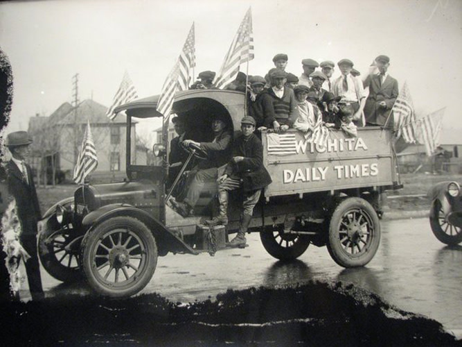 A historical photo showing a truck filled with people with American flags, bearing the name 'Wichita Daily Times' on the side