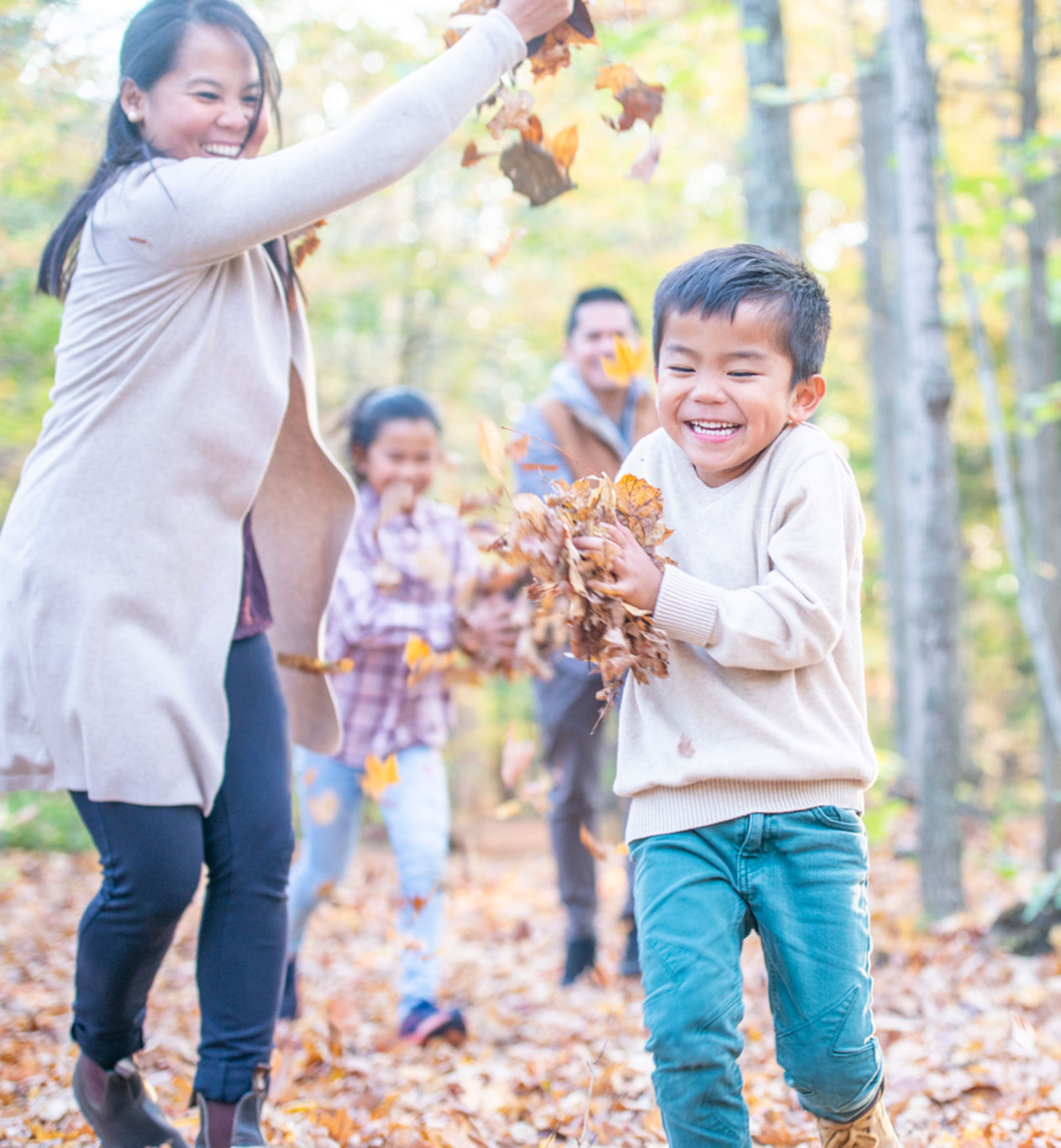 An Asian family plays in the leaves while on a walk in the woods.