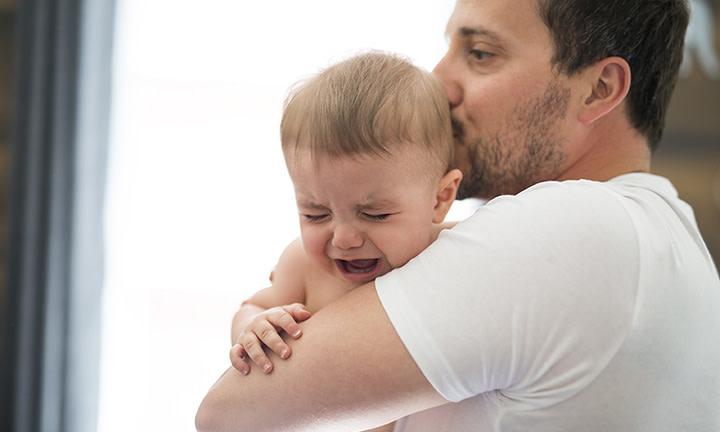Un bébé pleurant dans les bras de son père