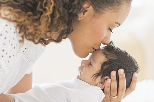 Maman embrassant son bébé sur le front