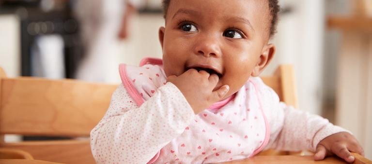 Bébé mordillant sa main suite au sevrage de l'allaitement