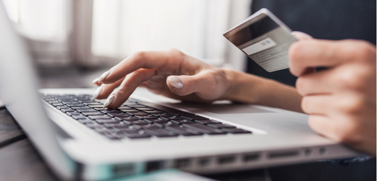 woman holding a credit card while shopping online