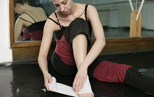 dancer taping her injured ankle