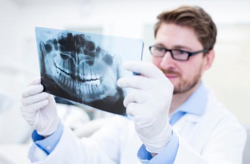 dentist examining a dental x-ray