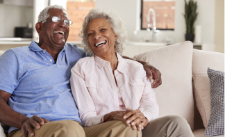 senior couple sitting on a couch laughing