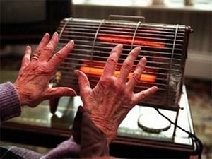 image of old woman's hands next to old style two-bar electric fire