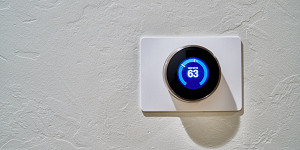 White wall with blue smart thermostat showing 63 degrees