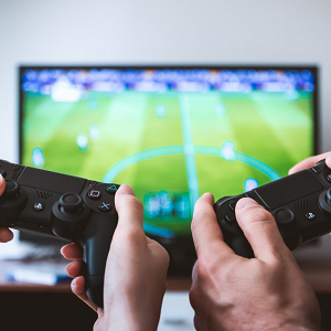 two PS4 video game controllers being held and playing a football game on TV