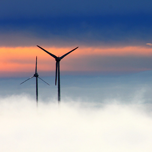 silhouette of two wind turbines in mist with blue and orange morning sky