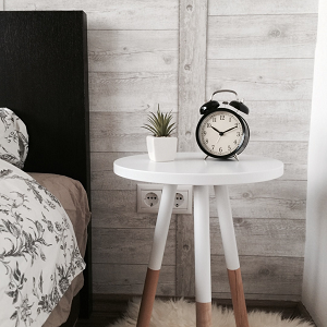 old style alarm clock on white bedside table