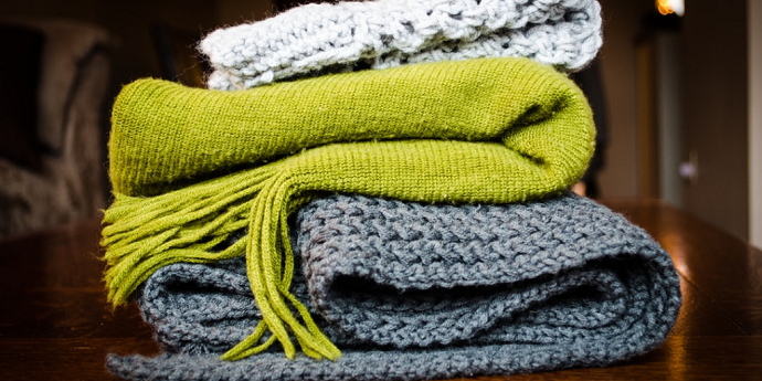 three scarfs in a pile, top one is white, middle is green, bottom is grey