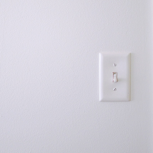 white plastic light switch on white wall