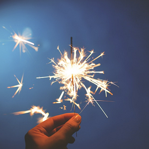 image of hand holding a sparkler with sparks