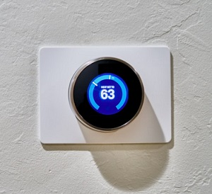 blue thermostat dial set to 63 degrees on white wall