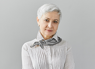 Grey Short Haired Woman with scarf against grey background