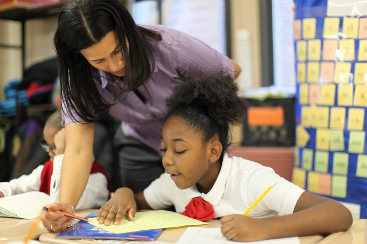 A teacher instructing a student in reading comprehension, using Readworks curricula.