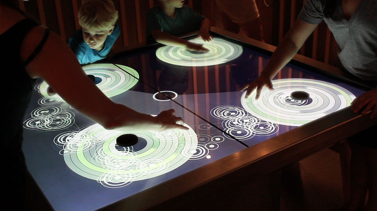 Visitors exploring harmonious sounds on the Circle of Fifths touch table.