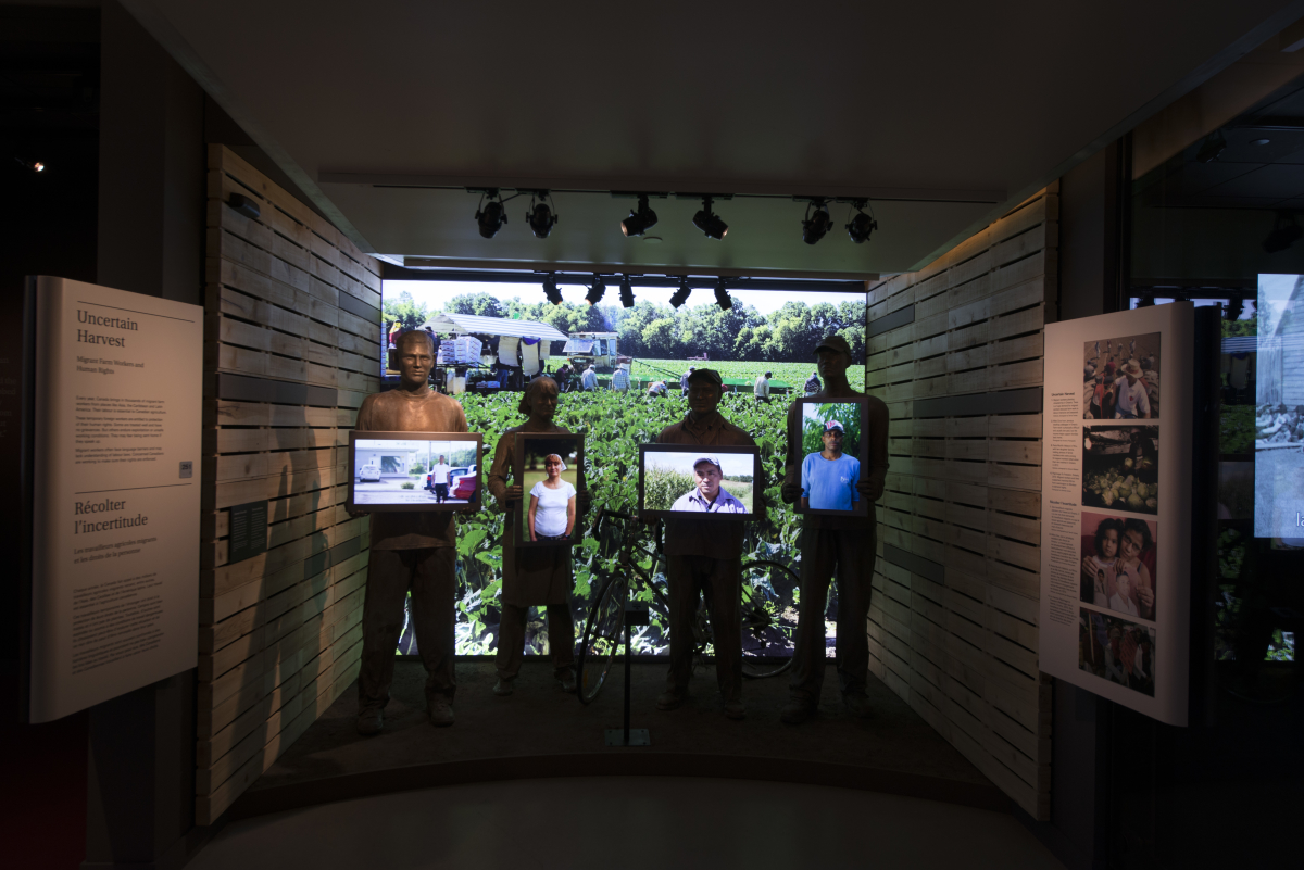 Screens carried by life-size replica of migrant workers.