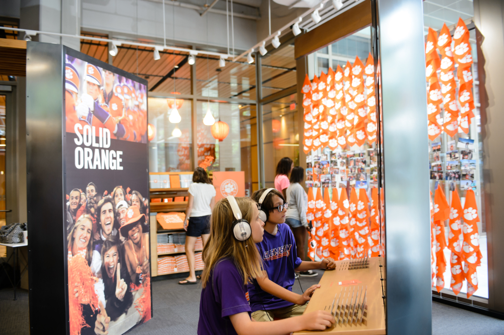 Visitors engage in perusing Clemson content, social images, and memorabilia at Experience Clemson.