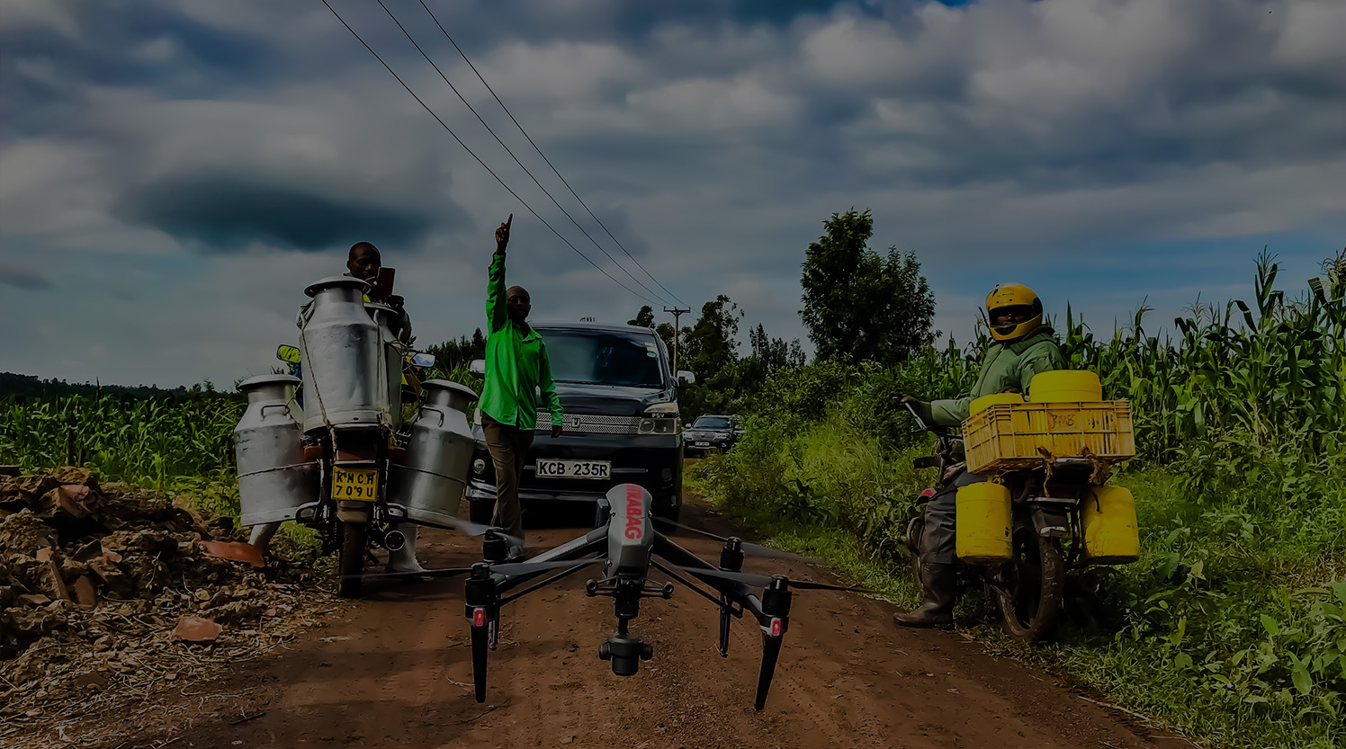 A group watching a drone take off to map a dam in Kenya