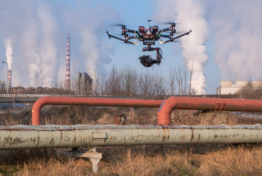 A drone with a camera hovering over a pipeline.