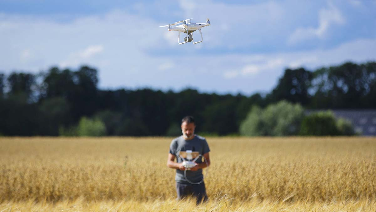 farmer flying a drone over an agriculture field