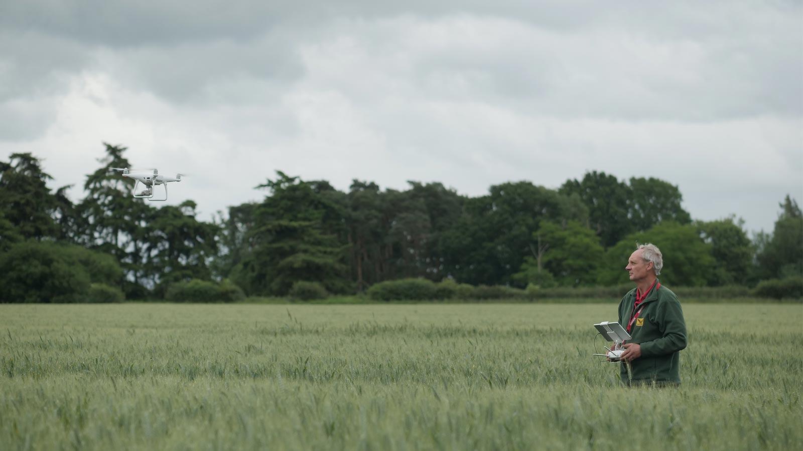 Farmer flying a drone in a field