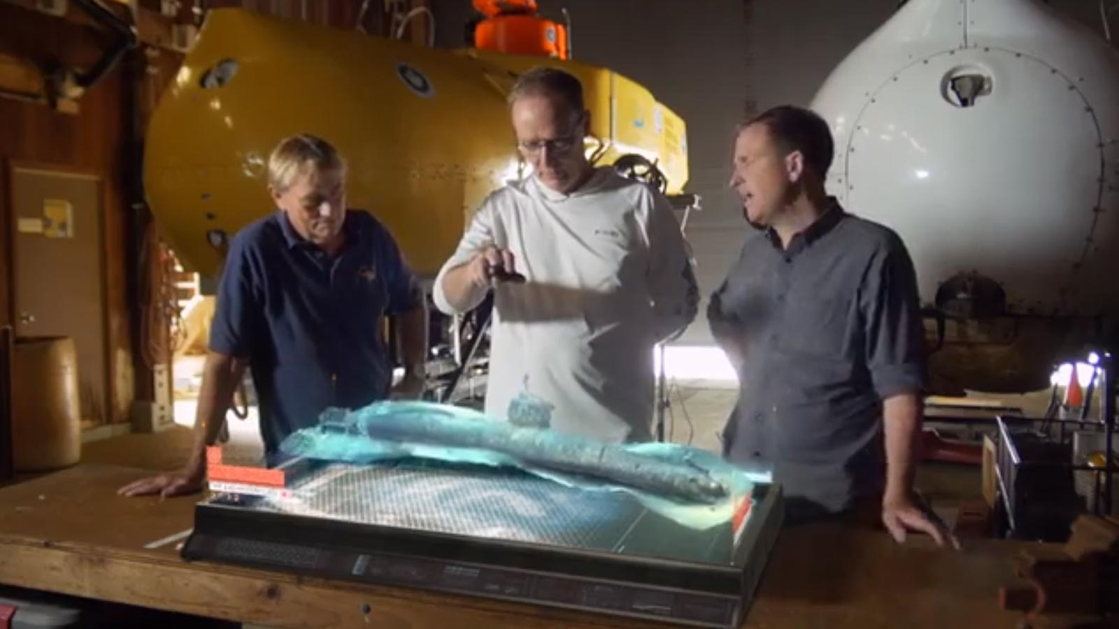 National Geographic team examining a 3D model of a submarine wreck
