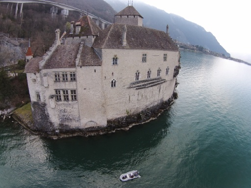 The facade of Castle Chillon captured from the lake. The boat is visible in the lake.