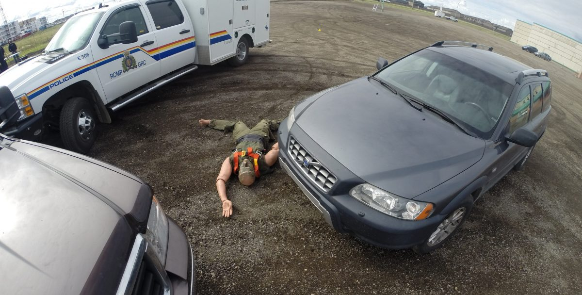 A demo crime scene, featuring a dummy on the ground surrounded by several cars.