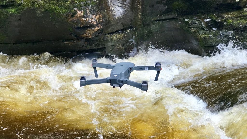 A drone hovers over river rapids
