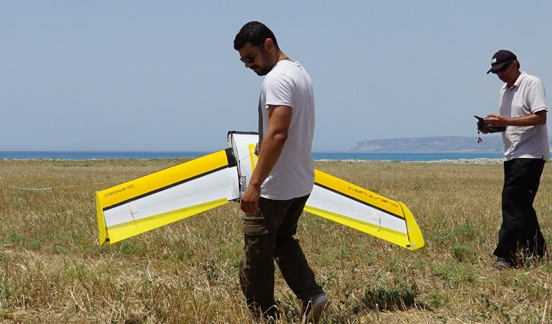 Team members holding a fixed-wing drone