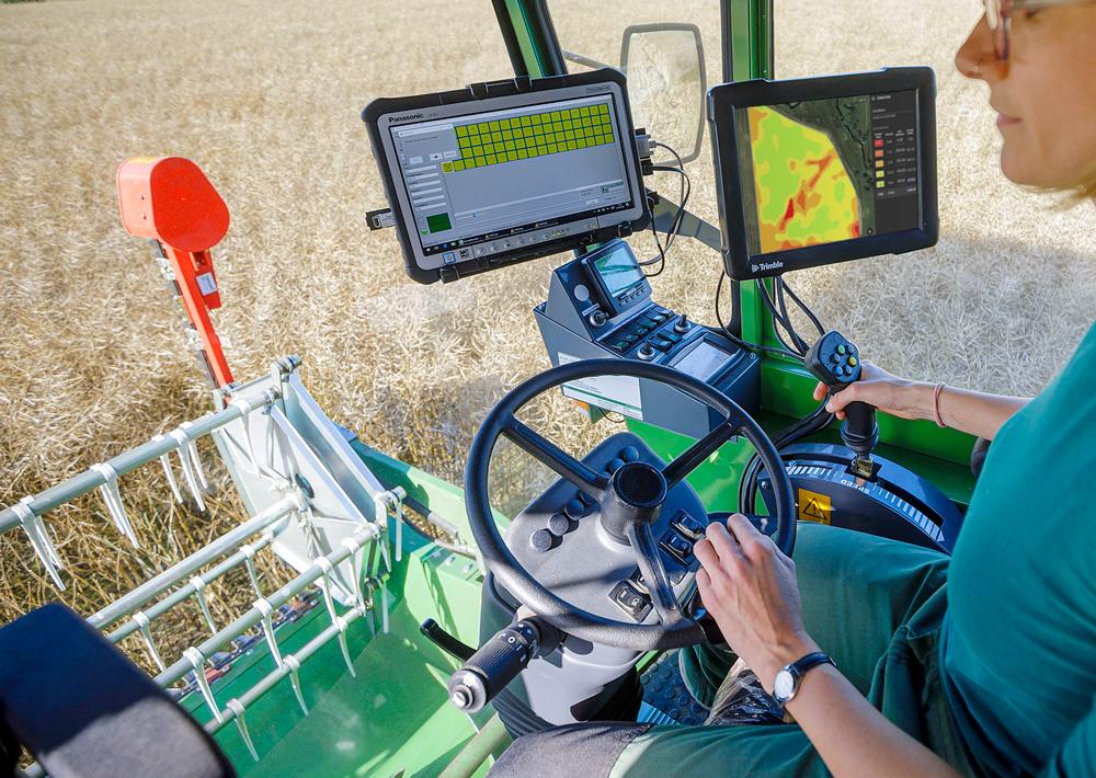 Landwirt mit Traktor und Planungssoftware zur teilflächenspezifischen Anwendung