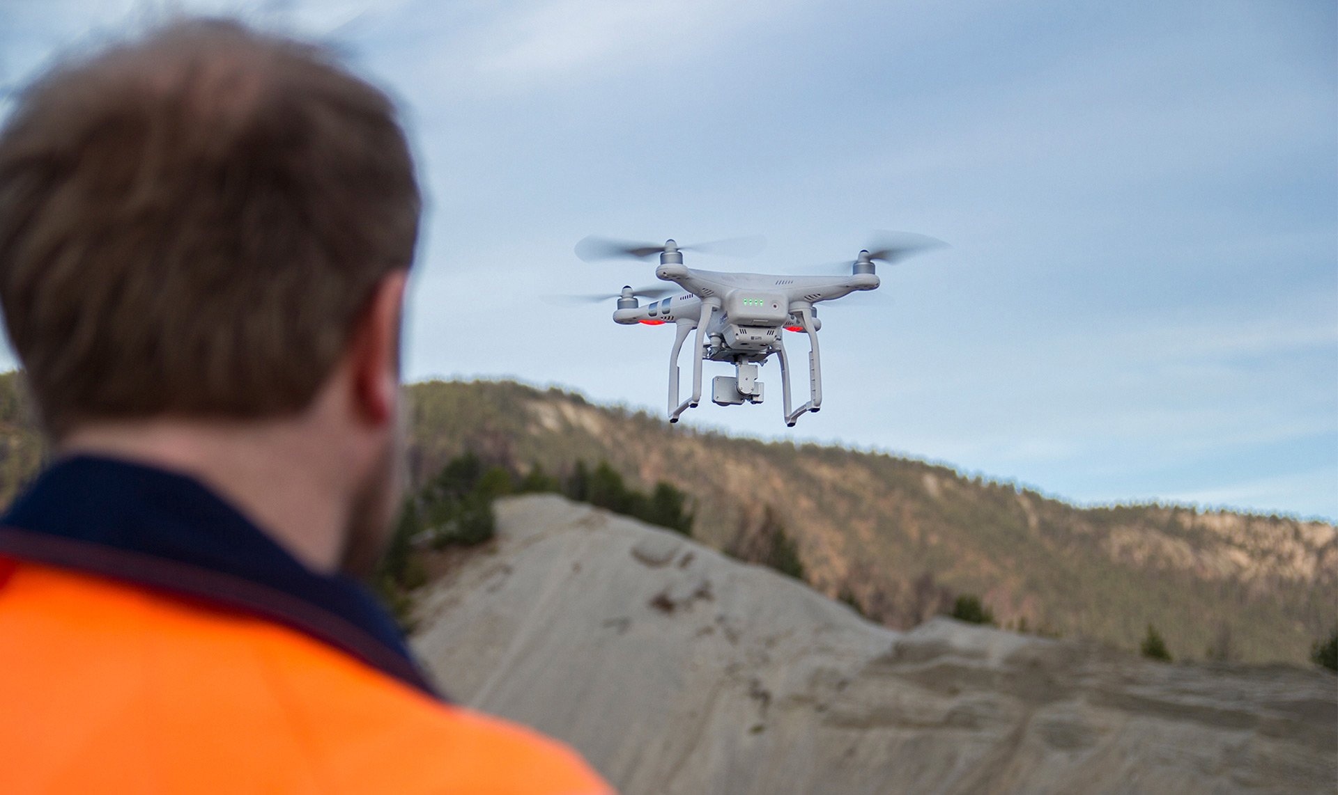 An Isachsen team member flying a drone over a construction site.