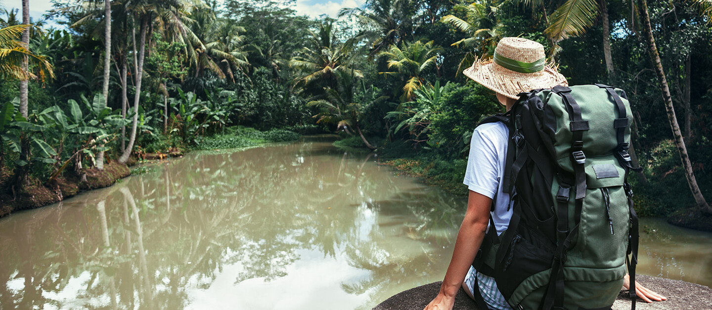 Backpacker travelling through jungle by boat