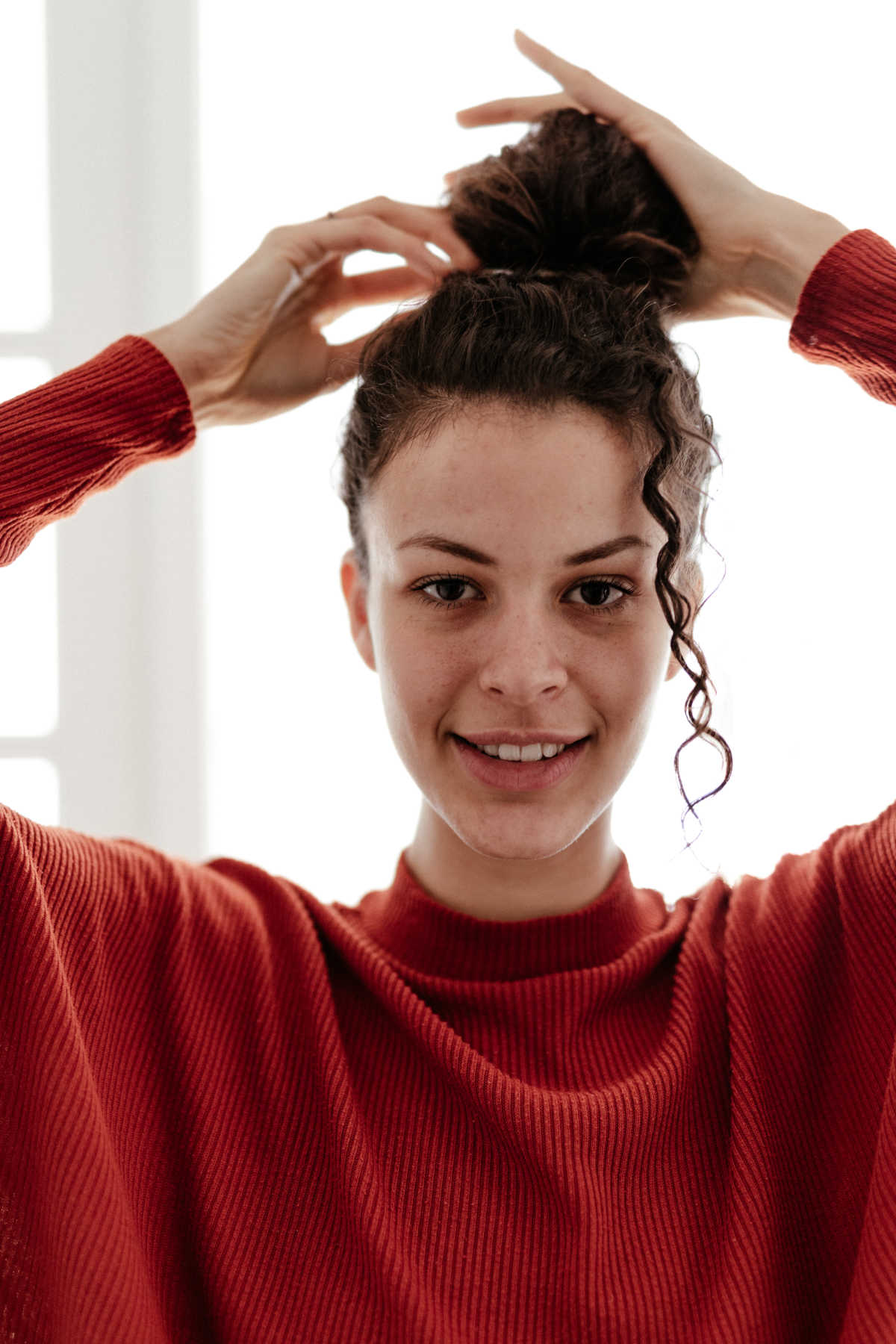 Young woman in red sweater smiles while adjusting her hair bun
