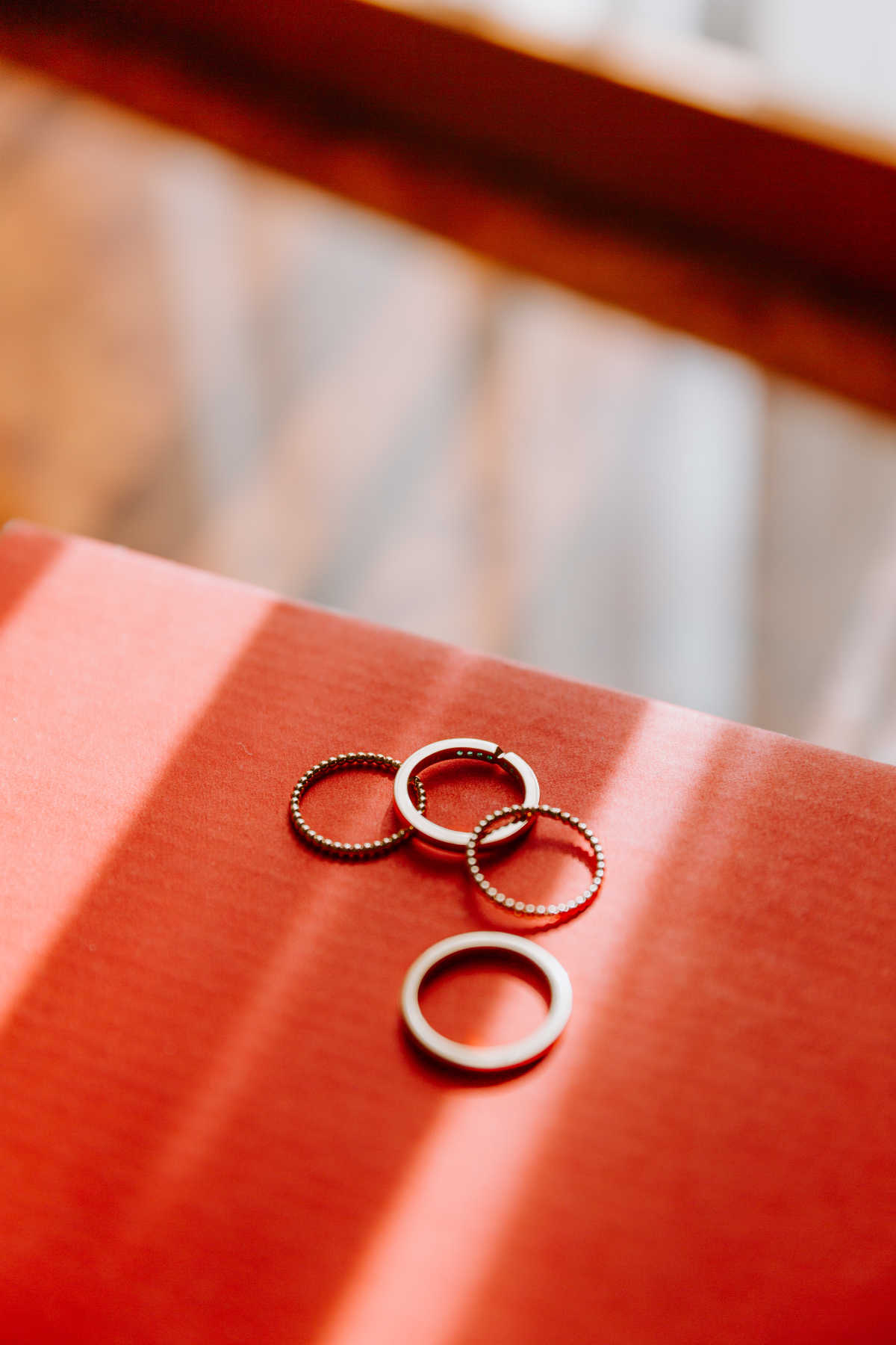 A set of four rings lying on a red surface