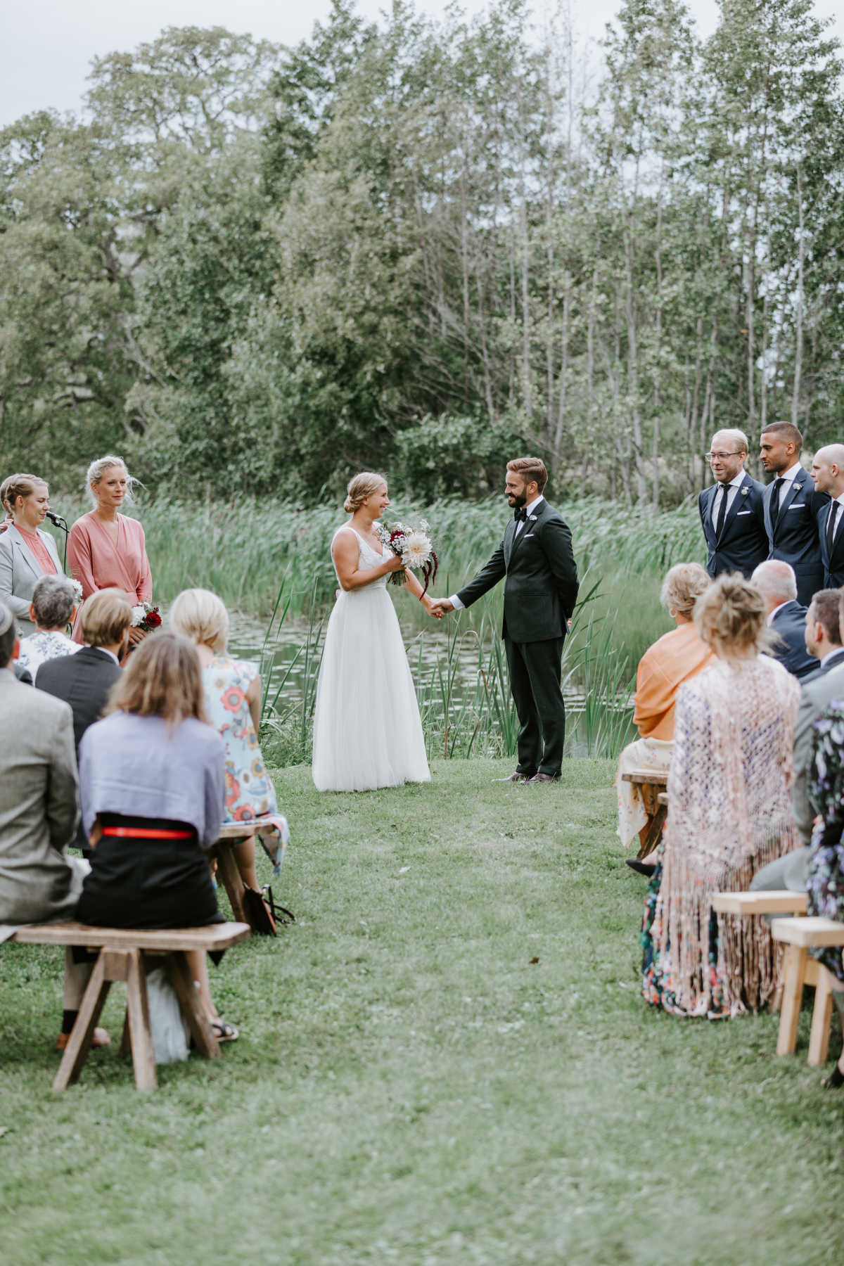 Photo of the reception. The brid and groom are standing in front of the seated guests. They are holding hands, smiling and looking at each other.