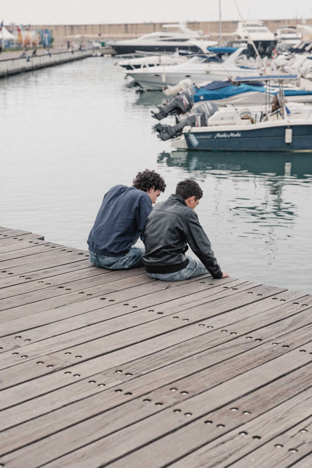 Two young boys sitting at a dock, looking into the water