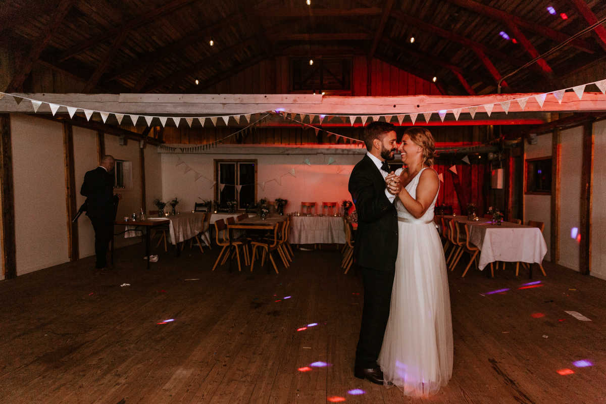 The bride and groom dancing inside the the barn
