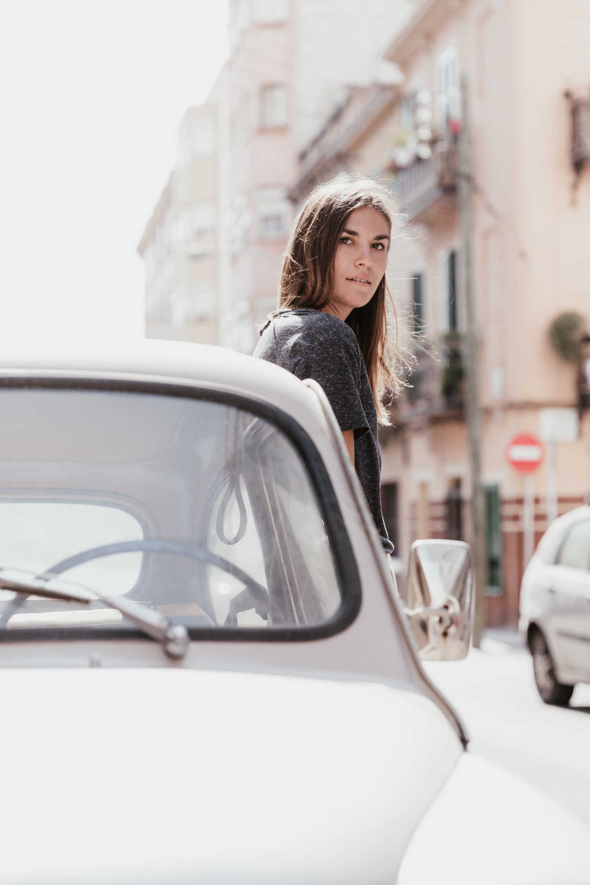 A woman looking into the camera while leaning against a classic car parked in the street