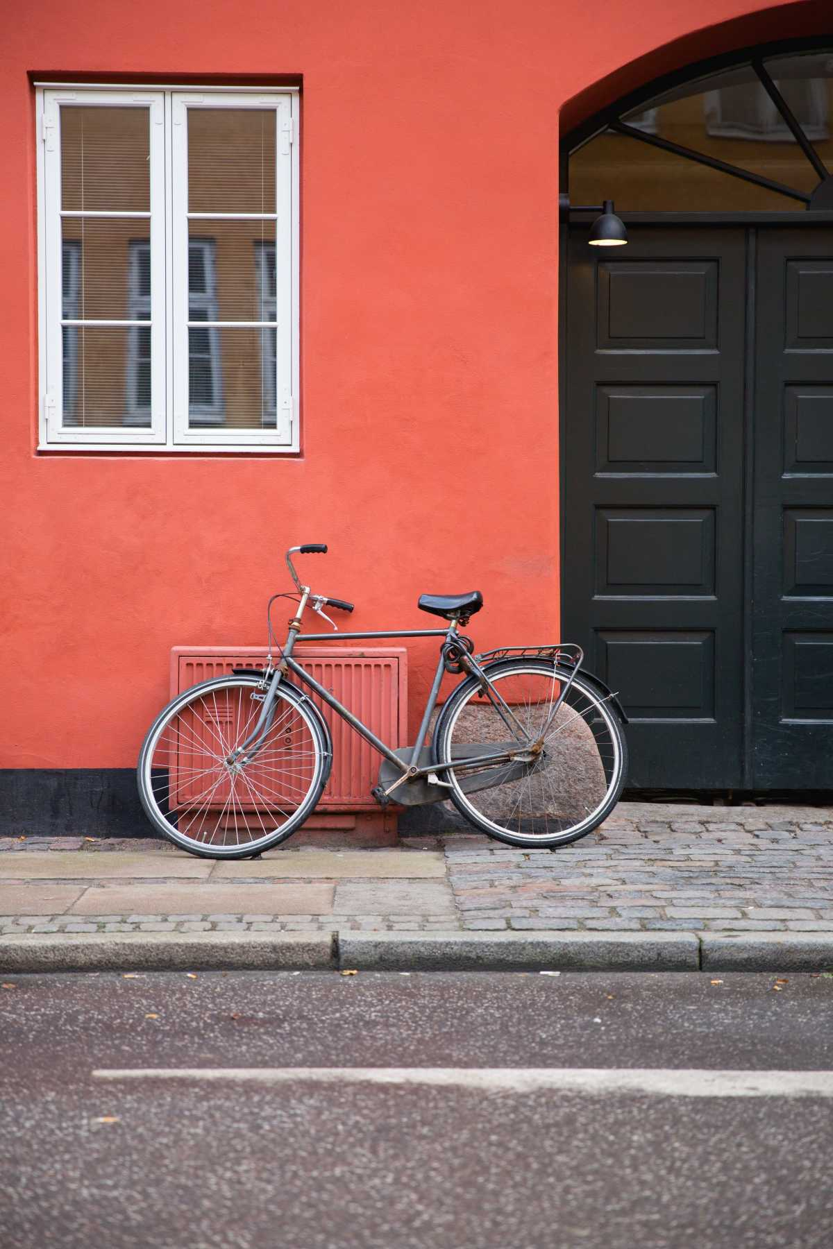A bicycle leans against an orange stone facade