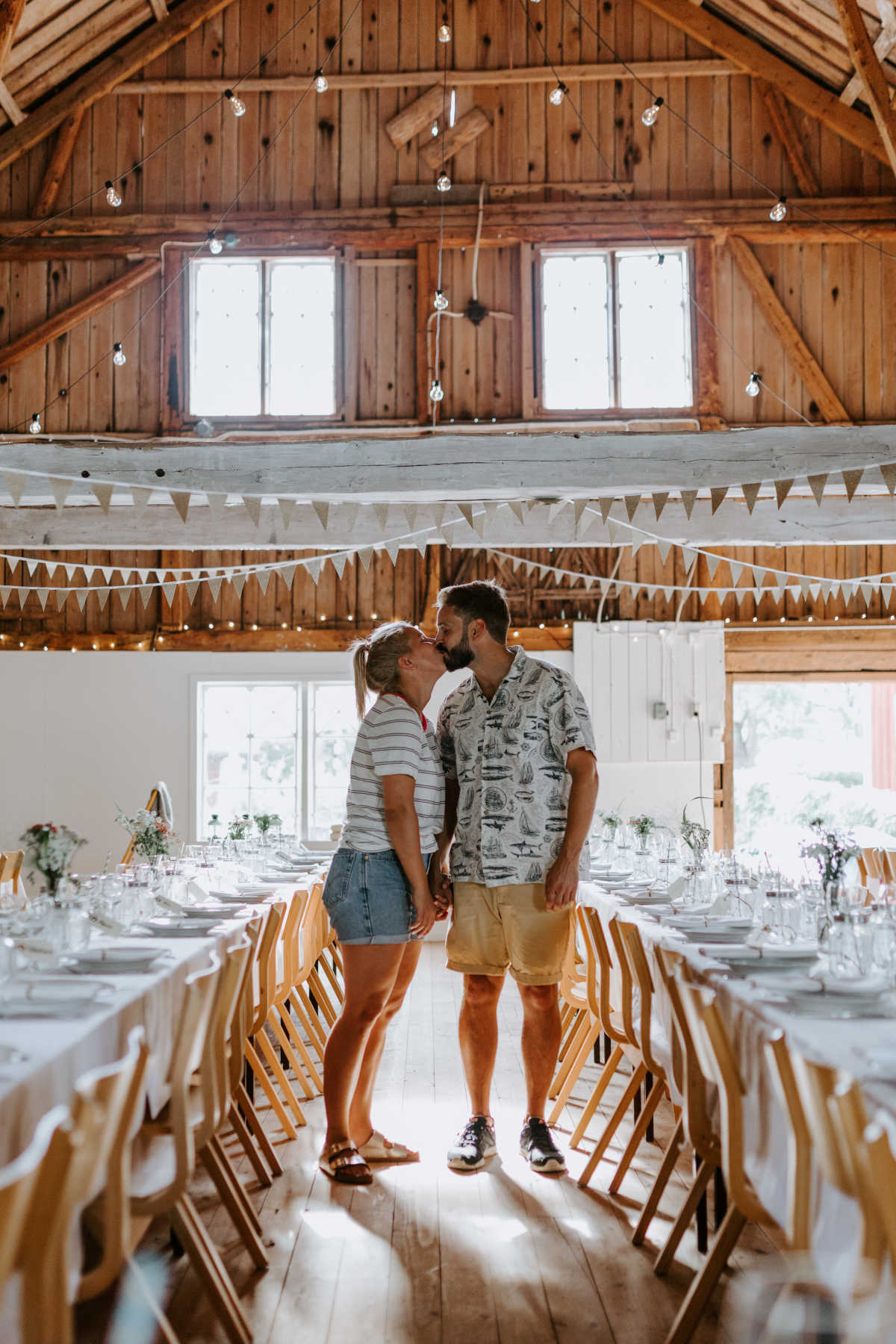 Casually dressed Julia and Jakob kissing inside the barn the day before the wedding
