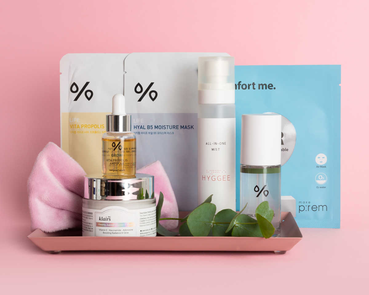 Various skincare products standing on a small plate against a pink background