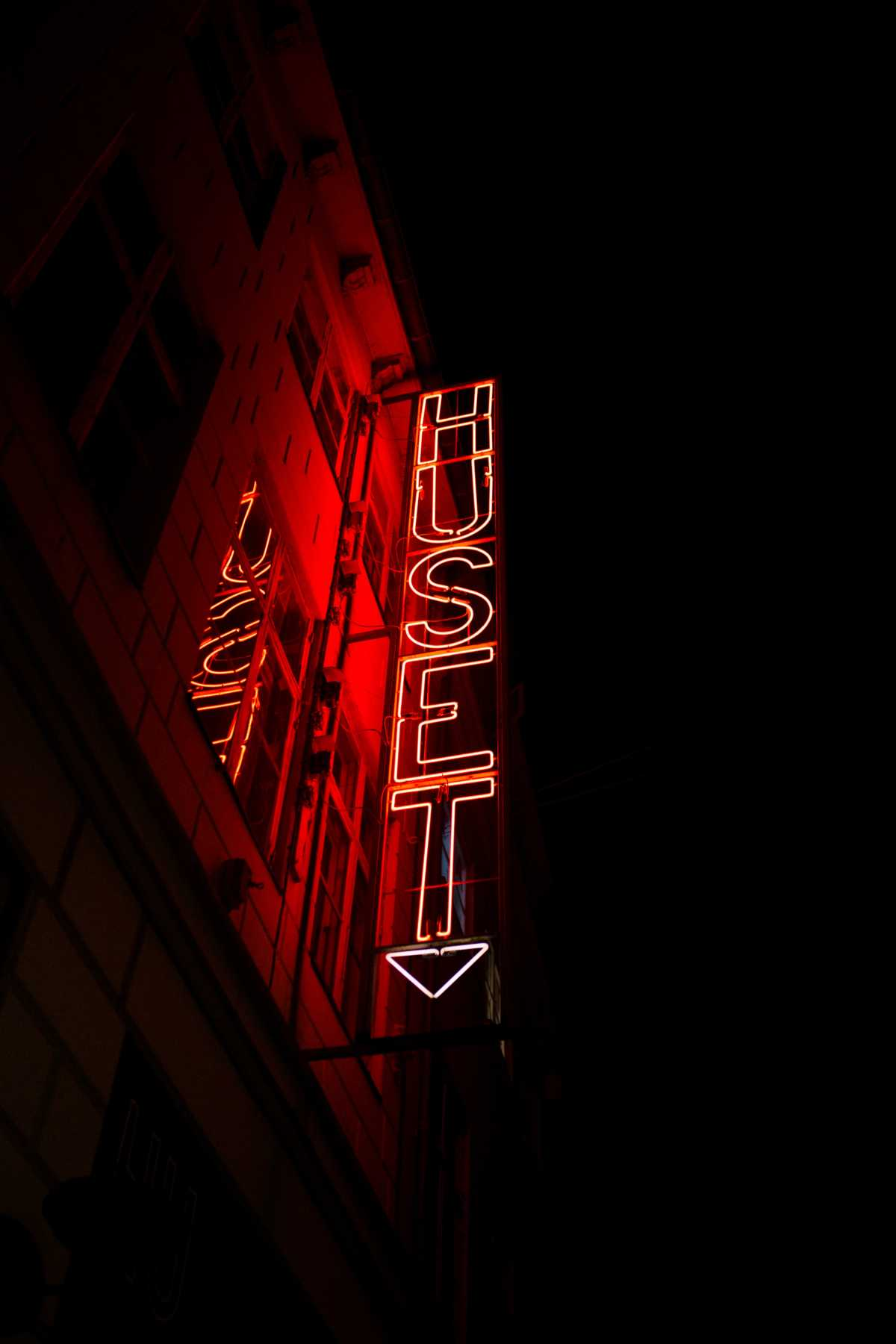 "A red neon sign lights up the night outside a building in Copenhagen. The sign reads ""huset"" – ""the house"", in Danish."