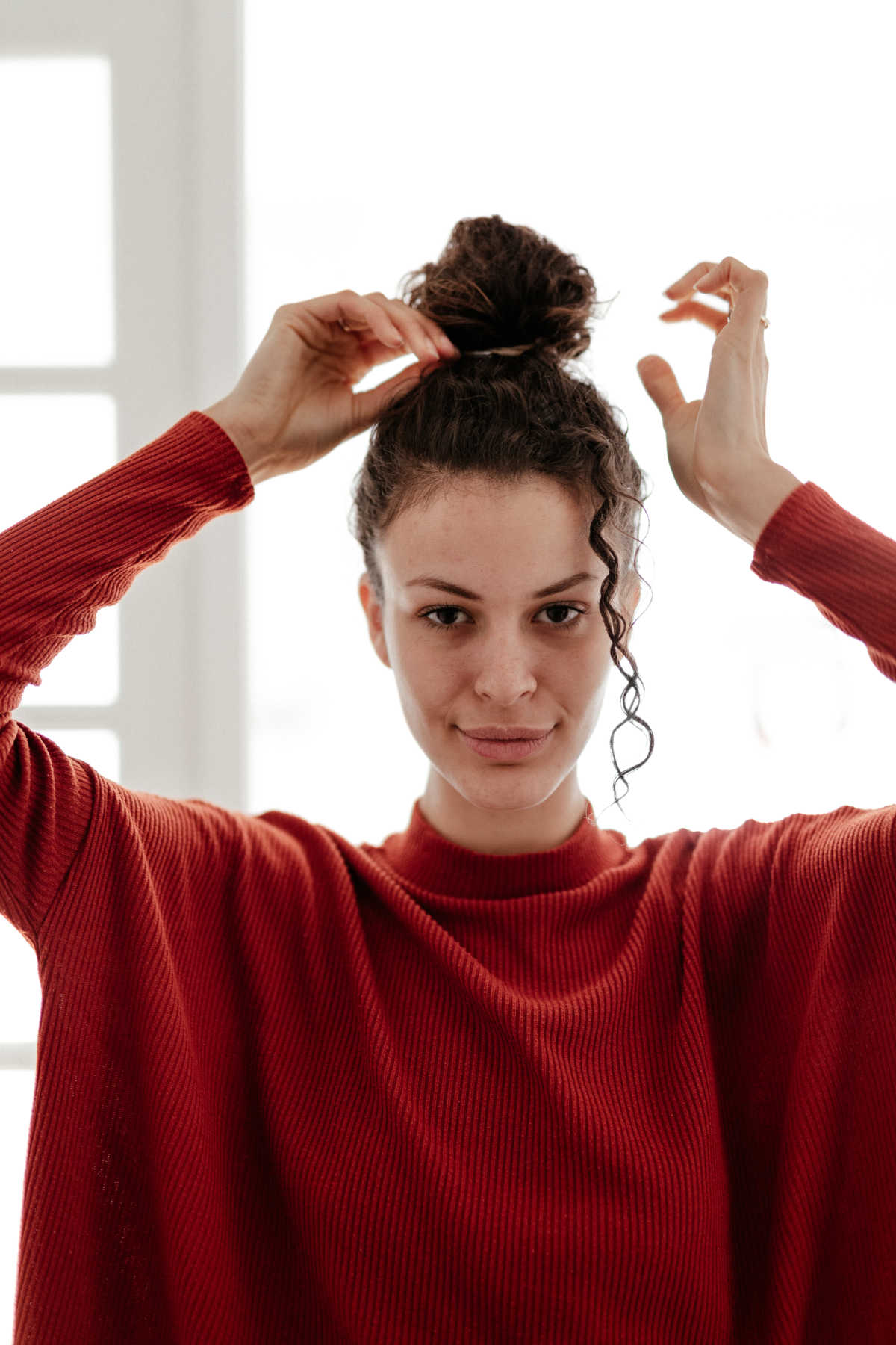 Young woman in red sweater adjusting her hair bun while looking into the camera