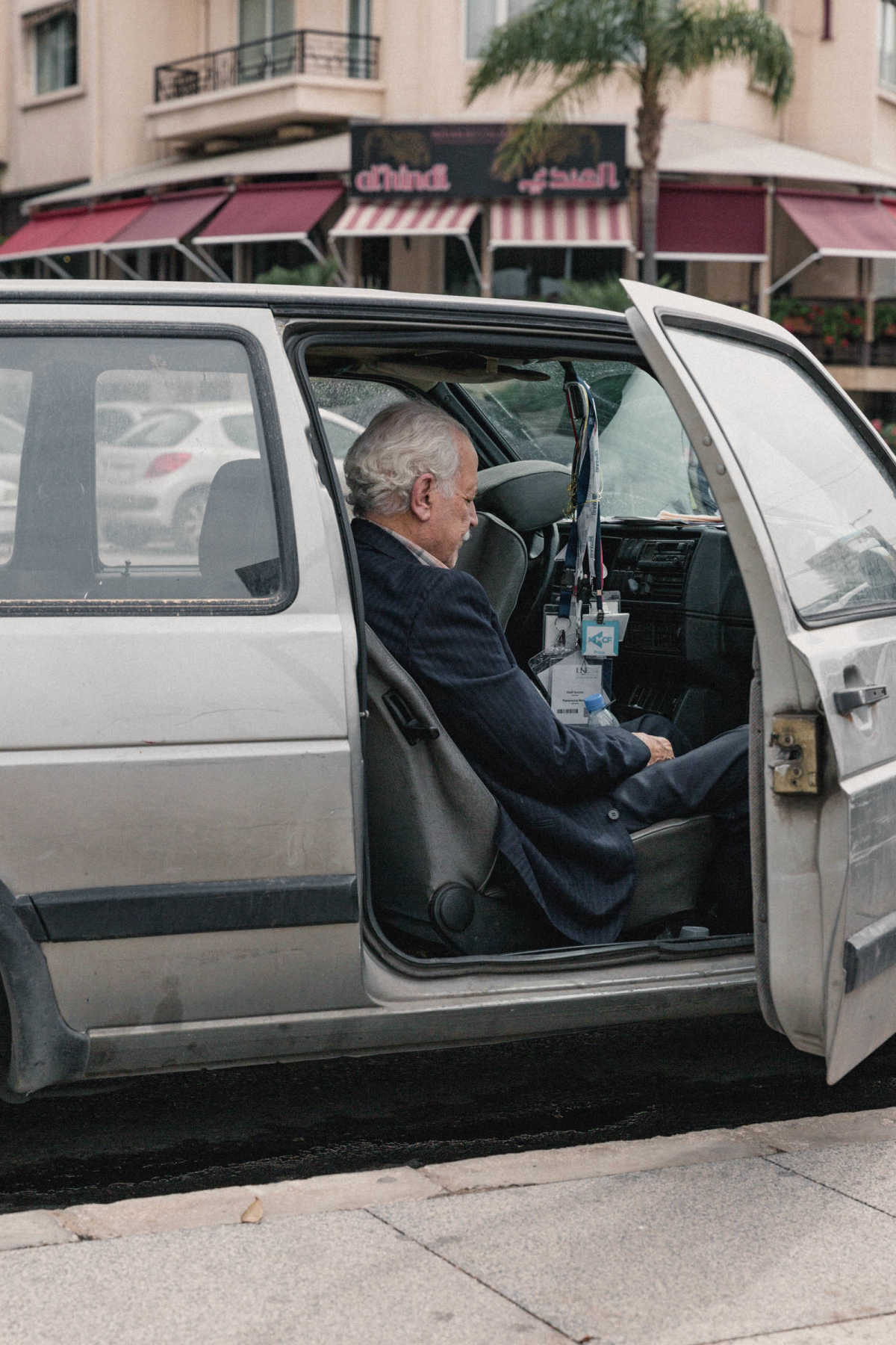 An old man resting in the passenger seat of a car