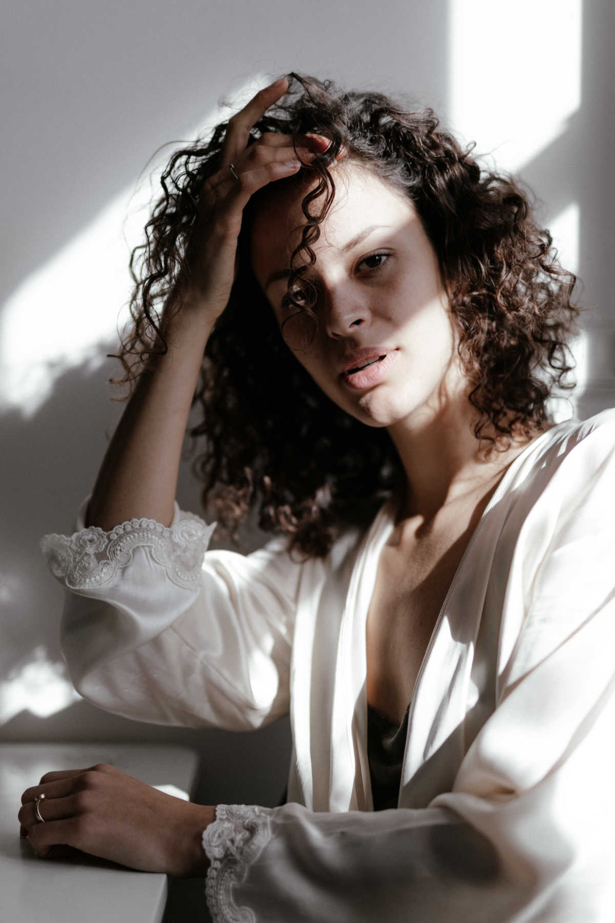 Young woman with curly hair sits by a table. Light from a nearby window casts strong shadows in her face.