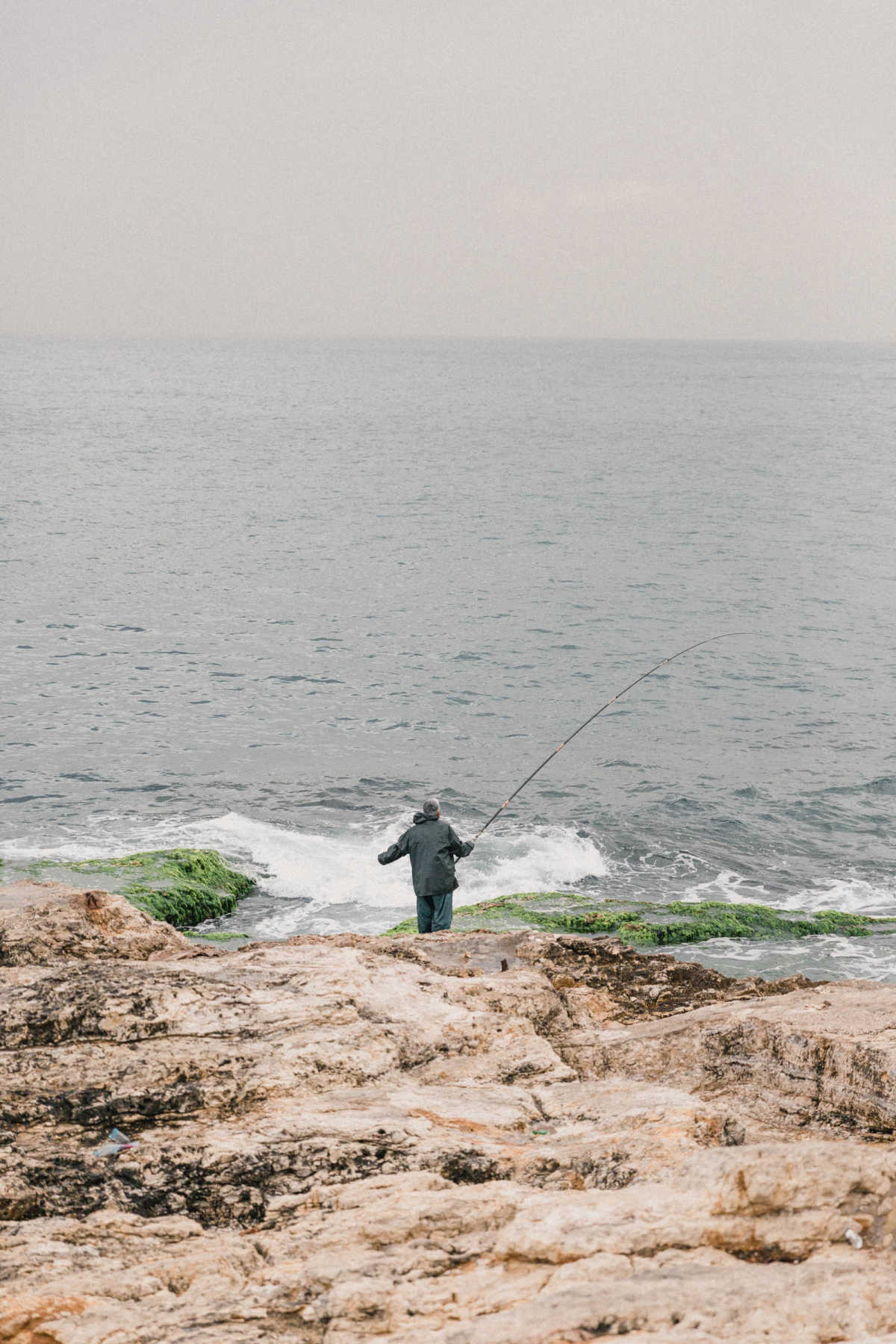 A man in full-body rain gear fishing. He stands on the rocks by the water as the waves come in.