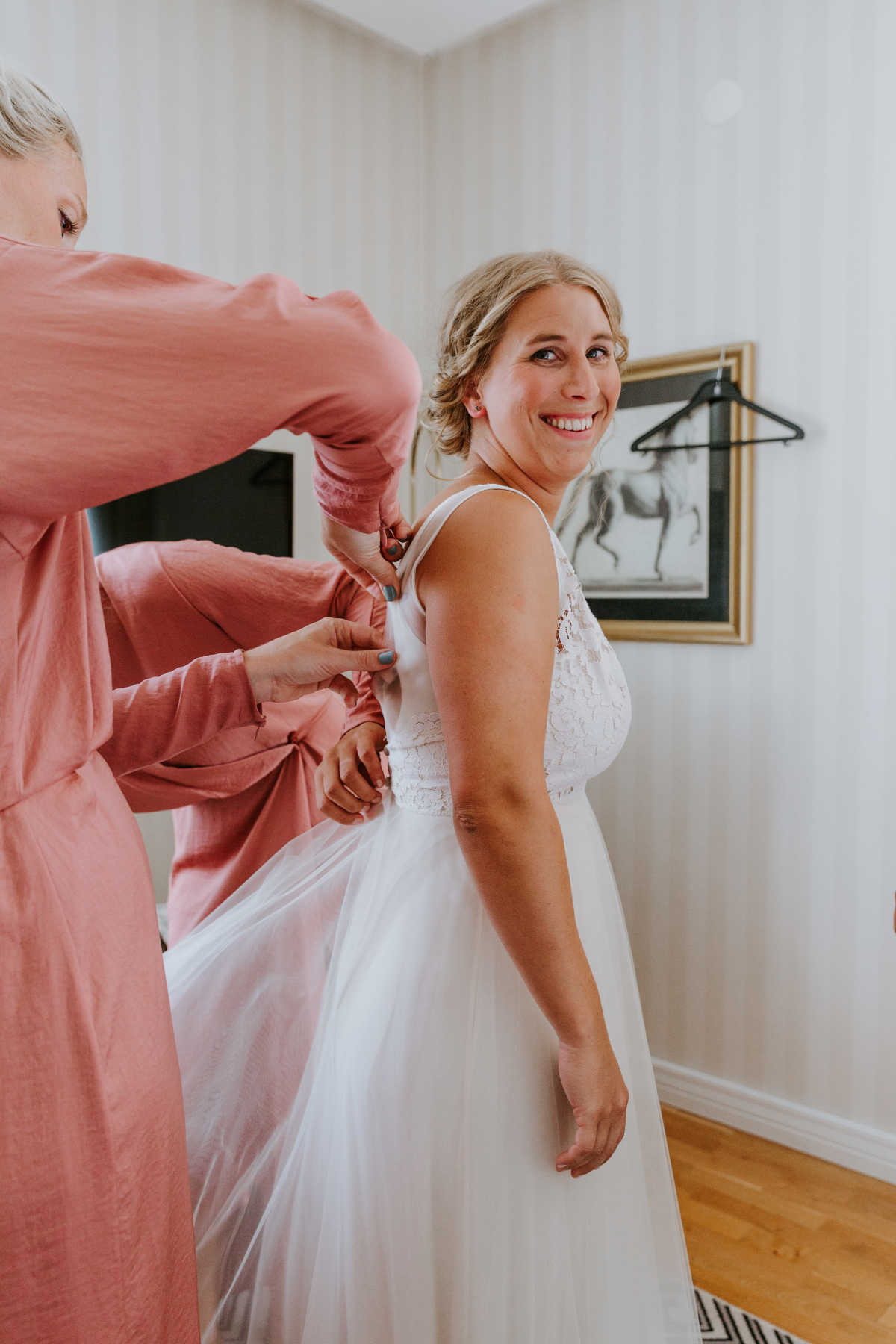 Julia, the bride, looks into the camera and smiles while the bridesmaids adjust her dress